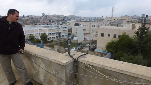 An IT teacher inspects an antenna on top of the Hebron Industrial Secondary School in Hebron, Palestine. Photo: Robert Marsh