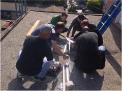 Twitter volunteers assembling wireless radio antenna mount.