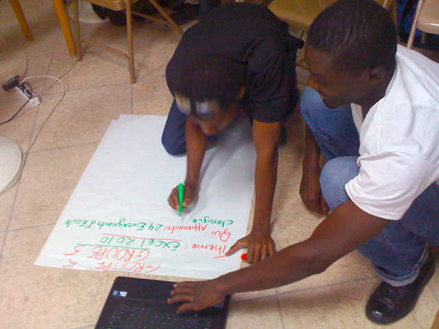 Mercidieu and a fellow community IT instructor prepare a lesson plan for a class on Microsoft Excel 2010.