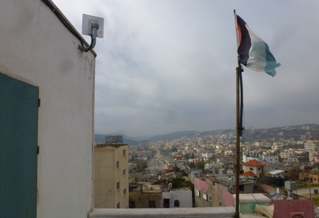 A high-speed wireless antenna sits alongside a Palestinian flag in Salfit, Palestine. Photo: Bob Marsh